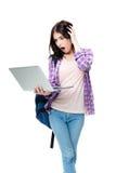 Mujer sorprendida que se coloca y que mira en la pantalla del ordenador portátil Imagenes de archivo