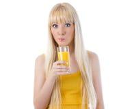 Mujer sorprendida que sorbe el zumo de naranja Fotografía de archivo