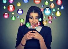 Mujer sorprendida que usa iconos sociales del smartphone los medios que vuelan hacia fuera la pantalla foto de archivo libre de regalías