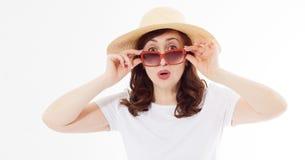 Mujer sorprendida y emocionada feliz en sombrero del verano, gafas de sol y la camiseta blanca de la plantilla aislada en el fond foto de archivo