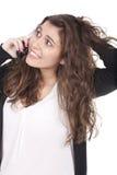 Mujer spealking en el teléfono y que se sostiene el pelo Foto de archivo