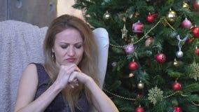 Mujer subrayada con dolor de cabeza en fondo del árbol de navidad Mujer joven triste interior metrajes