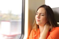 Mujer subrayada con el dolor del cuello en un carro del tren Fotografía de archivo libre de regalías