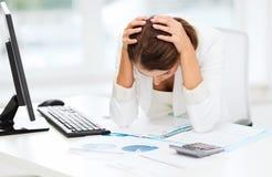 Mujer subrayada con el ordenador, papeles, calculadora Fotografía de archivo libre de regalías