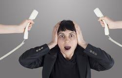 Mujer subrayada con el teléfono alrededor de su cabeza Fotos de archivo