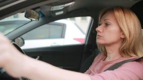 Mujer subrayada en el cigarrillo que fuma y la comprobación del coche del tiempo Coches en el asfalto almacen de video