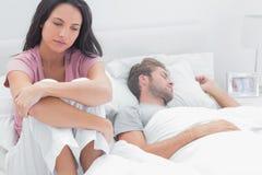 Mujer subrayada en su cama Imagenes de archivo