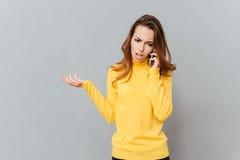 Mujer subrayada infeliz que habla en el teléfono móvil Fotografía de archivo libre de regalías