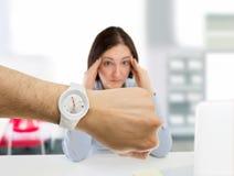 Mujer subrayada por la puntualidad en la oficina Fotos de archivo