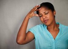 Mujer subrayada que lleva a cabo una mano en su cabeza Imagen de archivo