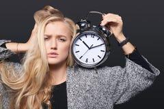 Mujer subrayada que sostiene el despertador grande fotografía de archivo