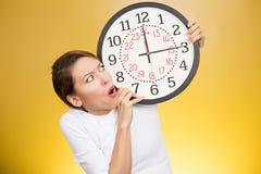 Mujer subrayada que sostiene el reloj que mira ansiosamente de funcionamiento de tiempo imagen de archivo