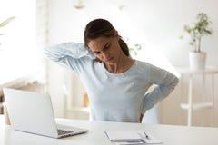 Mujer subrayada que tiene problema de salud, sintiendo espalda dolor fotos de archivo libres de regalías