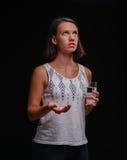 Mujer subrayada que toma meds en un fondo negro Drogas prescripted que toman femeninas Salud, vitaminas, concepto de la medicina Fotografía de archivo libre de regalías