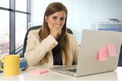 Mujer subrayada que trabaja con el ordenador portátil en el escritorio en con exceso de trabajo Imagenes de archivo