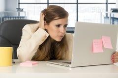 Mujer subrayada que trabaja con el ordenador portátil en el escritorio en con exceso de trabajo Imágenes de archivo libres de regalías