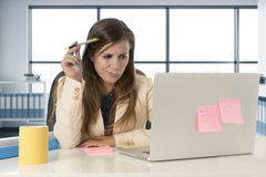 Mujer subrayada que trabaja con el ordenador portátil en el escritorio en con exceso de trabajo Foto de archivo