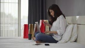 Mujer subrayada que usa el ordenador portátil para las compras en línea en cama, y teniendo problema con la tarjeta de crédito bl almacen de metraje de vídeo