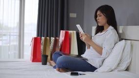Mujer subrayada que usa la tableta y teniendo problema para las compras en línea en dormitorio almacen de metraje de vídeo