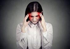 Mujer subrayada triste con dolor de cabeza Imagenes de archivo