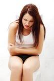 Mujer sufridora debido a dolor de estómago. Imagen de archivo