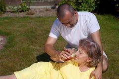 Mujer suministrada hombre con el golpe de calor Imagen de archivo