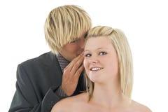 Mujer susurrante del hombre al oído. Fotos de archivo