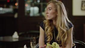 Mujer tímida del blondie en restaurante metrajes