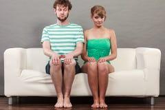 Mujer tímida y hombre que se sientan cerca de uno a en el sofá Foto de archivo libre de regalías