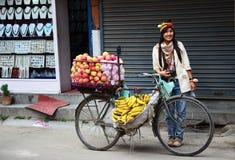 Mujer tailandesa con la tienda de la fruta de la bicicleta en Nepal Imagen de archivo libre de regalías