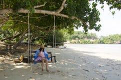 Mujer tailandesa que se sienta en el banco de madera del oscilación con el añil del mauhom Imagen de archivo libre de regalías