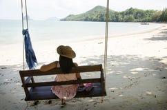 Mujer tailandesa que se sienta en el banco de madera del oscilación con el añil del mauhom Fotos de archivo libres de regalías