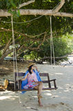Mujer tailandesa que se sienta en el banco de madera del oscilación con el añil del mauhom Foto de archivo libre de regalías