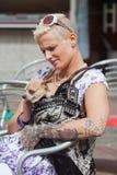 Mujer tatuada con un perro en el bolso foto de archivo libre de regalías