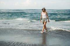 Mujer tatuada que camina en la playa Imagen de archivo