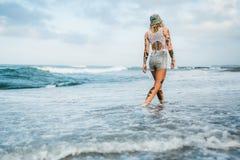 Mujer tatuada que camina en la playa Imagenes de archivo