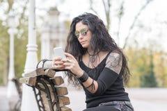 Mujer tatuada que se sienta en banco y que usa el teléfono elegante en la calle fotos de archivo