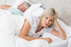 Mujer tensada que miente además de hombre en cama Fotografía de archivo