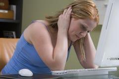 Mujer tensada que se sienta en el escritorio del ordenador Foto de archivo