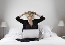 Mujer tensionada con la computadora portátil Fotos de archivo libres de regalías