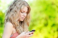 Mujer texting en el teléfono móvil Imágenes de archivo libres de regalías