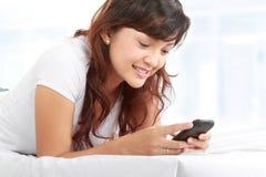 Mujer texting en el teléfono que miente en cama Imagen de archivo