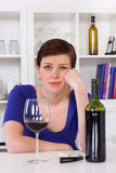 Mujer thinkful triste joven que bebe un vidrio de vino rojo Fotos de archivo libres de regalías