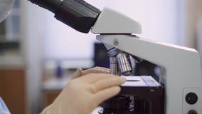 Mujer, trabajador médico con un microscopio en el laboratorio Ella está estudiando un análisis de sangre, o una mancha biológica  metrajes