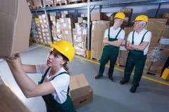 Mujer trabajadora y compañeros de trabajo perezosos Imagen de archivo libre de regalías