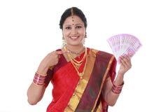 Mujer tradicional que lleva a cabo nuevas 2000 notas de la rupia Imagen de archivo libre de regalías