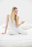 Mujer tranquila atractiva que usa su smartphone que se sienta en su cama Fotografía de archivo libre de regalías