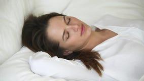 Mujer tranquila con la cara hermosa que duerme bien en cama cómoda almacen de metraje de vídeo