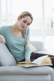 Mujer tranquila contenta que lee un libro mientras que se sienta en el sofá Fotografía de archivo libre de regalías