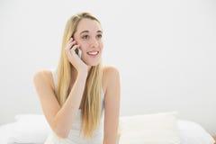 Mujer tranquila hermosa que se sienta en su cama mientras que llama por teléfono Imágenes de archivo libres de regalías